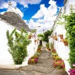 98042901-alberobello-italy-beautiful-town-of-alberobello-with-trulli-houses-among-green-plants-and-flower